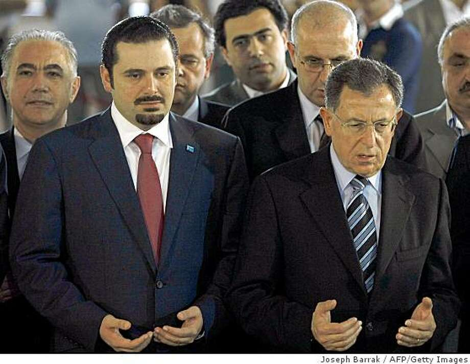 Outgoing Lebanese prime minister Fuad Siniora (R) and premier-designate Saad Hariri pray over the tomb of the latter's father, slain former prime minister Rafiq Hariri, in Beirut on June 27, 2009. Hariri, who was propelled into the heart of Lebanese politics following the assassination of his father four years ago, was himself named to the top job on June 27. AFP PHOTO/JOSEPH BARRAK (Photo credit should read JOSEPH BARRAK/AFP/Getty Images) Photo: Joseph Barrak, AFP/Getty Images