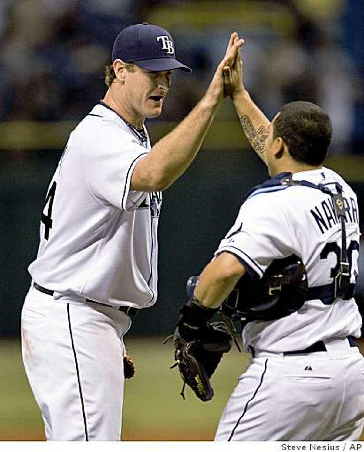 Tampa Bay Rays starter Jeff Niemann celebrates with catcher Dioner Navarro (30) after the final out of Niemann's 6-0 complete game shut out over the Oakland Athletics during a baseball game, Friday, July 10, 2009, in St. Petersburg, Fla. (AP Photo/Steve Nesius)