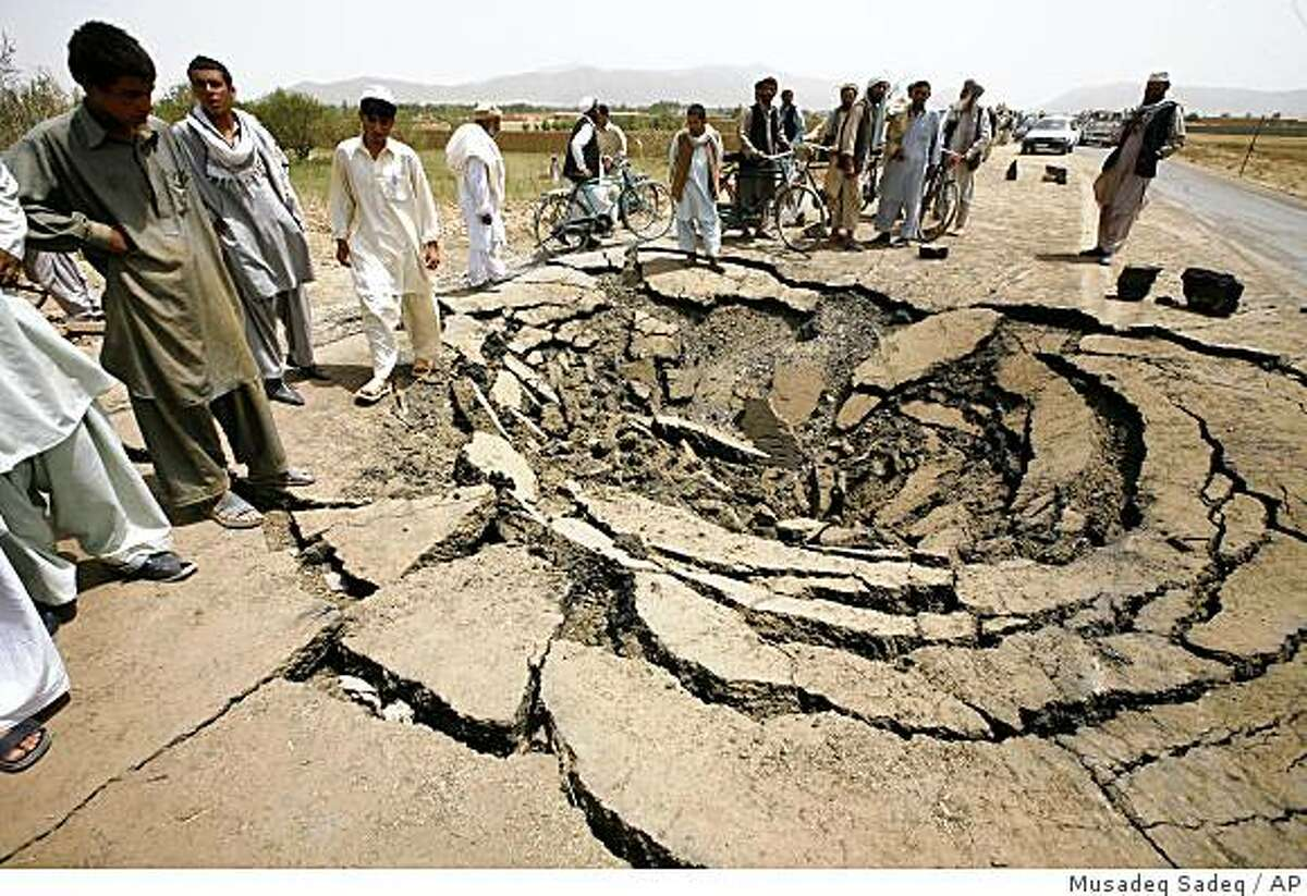 Afghans stand around the crater caused by a bomb blast in Mohammad Agha district on the main road from Kabul to Logar province, Afghanistan, Thursday, July 9, 2009. The blast killed 25 people including 13 primary school students, destroying shops and scattering pieces of the vehicle that carried the explosives over a huge area, police said. (AP Photo/Musadeq Sadeq)