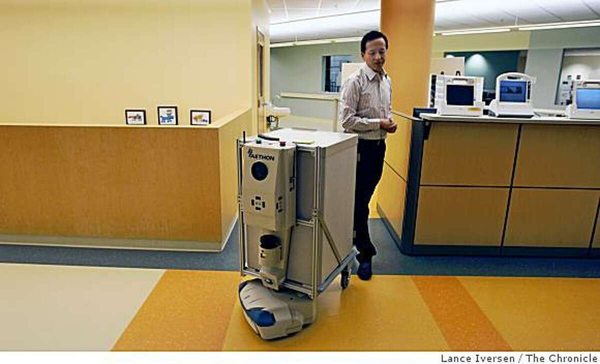 Sean Chai Senior IT Manager at Kaiser Permanente Garfield Health Care Innovation Center walks behind a Hospital Currier Robot that's programmed to deliver medications to a number of nurse's stations and or patient rooms. Wednesday June 24, 2009.