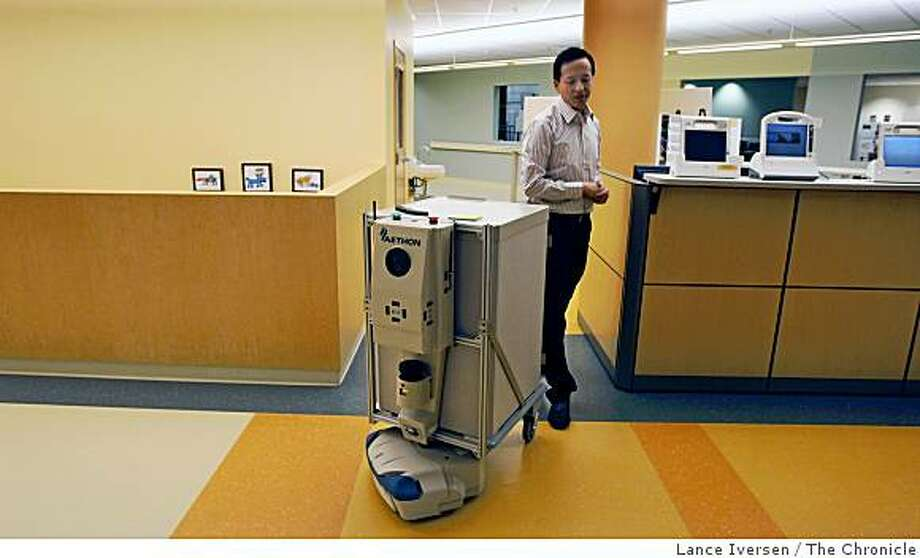 Sean Chai Senior IT Manager at Kaiser Permanente Garfield Health Care Innovation Center walks behind a Hospital Currier Robot that's programmed to deliver medications to a number of nurse's stations and or patient rooms. Wednesday June 24, 2009. Photo: Lance Iversen, The Chronicle
