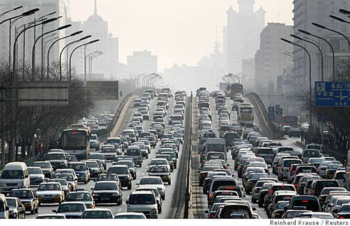 Cars are driven on one of the ring roads in Beijing's city centre in this January 15, 2008 file photo. Officials reportedly plan to keep half of Beijing's 3 million cars off the roads during the Games, which begin August 8. Authorities have also ordered Beijing and five surrounding provinces to cut industrial pollution for two months from late July. Picture taken January 15, 2008. To match feature OLYMPICS-BEIJING/POLLUTION REUTERS/Reinhard Krause (CHINA)