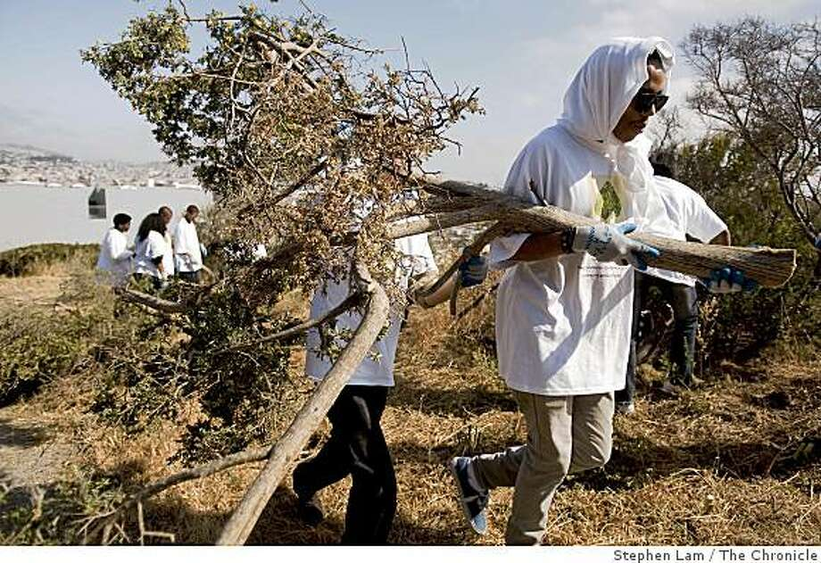 Kendall Jackson, 18, right, and Obdulio Carreras, 18, of Los Angeles, Calif. carries a small French Broom, an invasive plant, at Bayview Hill Park in San Francisco, Calif. on Friday, June 26, 2009. Both Jackson and Carreras are members of Jack and Jill of America Inc. and part of more than 350 high school seniors the gathered for the organization's annual teen leadership conference in San Francisco this weekend. Photo: Stephen Lam, The Chronicle