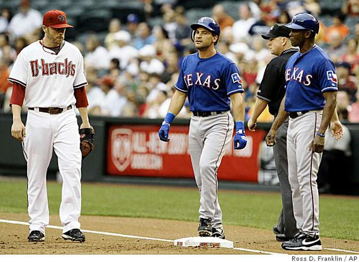 Texas Rangers' Omar Vizquel, center, of Venezuela, stands on first base after hitting a single, as Arizona Diamondbacks' Mark Reynolds, left, and Rangers coach Gary Pettis look on in the first inning of a baseball game Thursday, June 25, 2009, in Phoenix. Vizquel's single was his 2,678th career hit, the most ever by a native of Venezuela. (AP Photo/Ross D. Franklin)