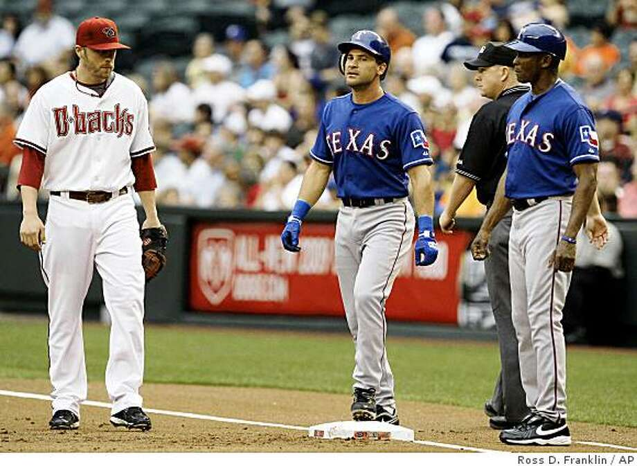 Texas Rangers' Omar Vizquel, center, of Venezuela, stands on first base after hitting a single, as Arizona Diamondbacks' Mark Reynolds, left, and Rangers coach Gary Pettis look on in the first inning of a baseball game Thursday, June 25, 2009, in Phoenix.  Vizquel's single was his 2,678th career hit, the most ever by a native of Venezuela. (AP Photo/Ross D. Franklin) Photo: Ross D. Franklin, AP