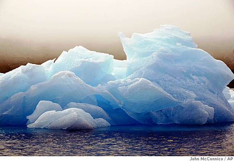 "FILE -  The July 17, 2007 file photo shows an iceberg floating in a bay off Ammassalik Island, Greenland. Sweeping legislation to curb the pollution linked to global warming and create a new energy-efficient economy is headed to an uncertain future in the Senate after squeaking through the House. The vote was a big win for President Barack Obama, who hailed House passage as a ""historic action."" ""It's a bold and necessary step that holds the promise of creating new industries and millions of new jobs, decreasing our dangerous dependence on foreign oil and strictly limiting the release of pollutants that threaten the health of families and communities and the planet itself,"" Obama said in a statement on Friday, June 26, 2009. (AP Photo/John McConnico, file) Photo: John McConnico, AP"