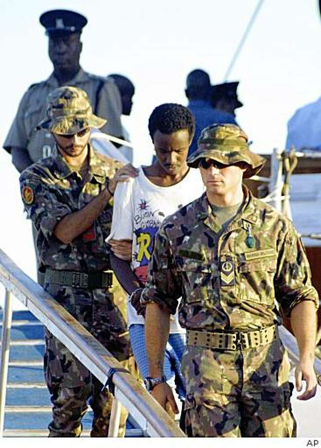 One of the nine suspected Somali pirates, second from right, is disembarked from an Italian warship MV Maestrale at the port of Mombasa, Kenya Thursday, June 25, 2009. The suspected pirates were arrested by the Italian naval officers along the Gulf of Eden as they attempted to hijack a cargo ship MV Marie K which was headed to Ireland from Abu Dhabi.  They will be taken to a court in Mombasa on Friday. (AP Photo) Photo: AP