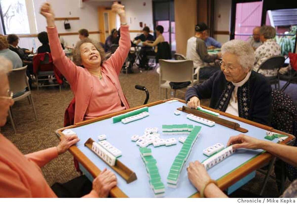 Jane Louie, 80, puts her hands in up fun and frustration after her long-time friend Michi Handa, 77, calls mahjong during the weekly meeting of the Fremont Senior Center Mahjong Group. Members say they look forward to Wednesdays at the center in Fremont, Calif. because it keeps them connected to each other in their aging-friendly community. Photographed in Fremont, CA on 2/20/08. photo by Mike Kepka / San Francisco Chronicle Ran on: 02-21-2008 Jane Louie puts up her hands after friend Michi Handa calls mahjong at the Fremont Senior Center, considered a model aging-friendly community.