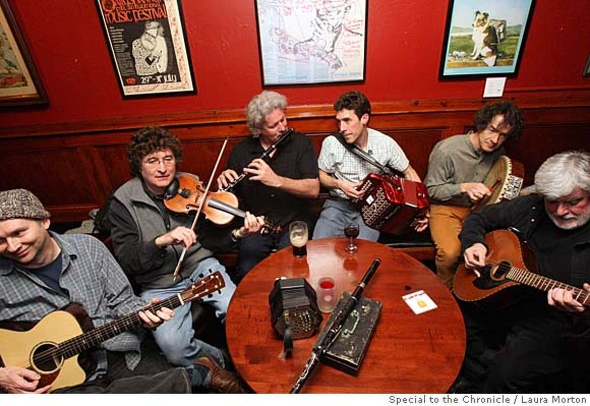 Kenny Sommerville, John Caulfield, Vinny Cronin, Barry O'Connell, Cormac Gannon and Vincy Keehan (left to right), who make up the lively Irish band The Gasmen, break into an impromptu jam session while sitting for a portrait at Plough and Stars in San Francisco. (Laura Morton/Special to the Chronicle)