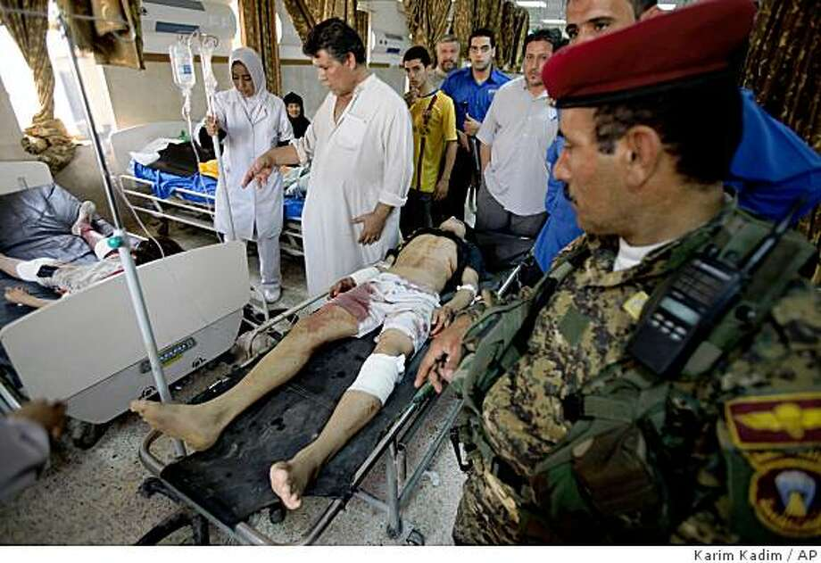 An Iraqi soldier is seen in a hospital as a wounded man arrives for treatment after a roadside bomb attack near a market in the Shiite enclave of Sadr City in Baghdad, Iraq. Photo: Karim Kadim, AP