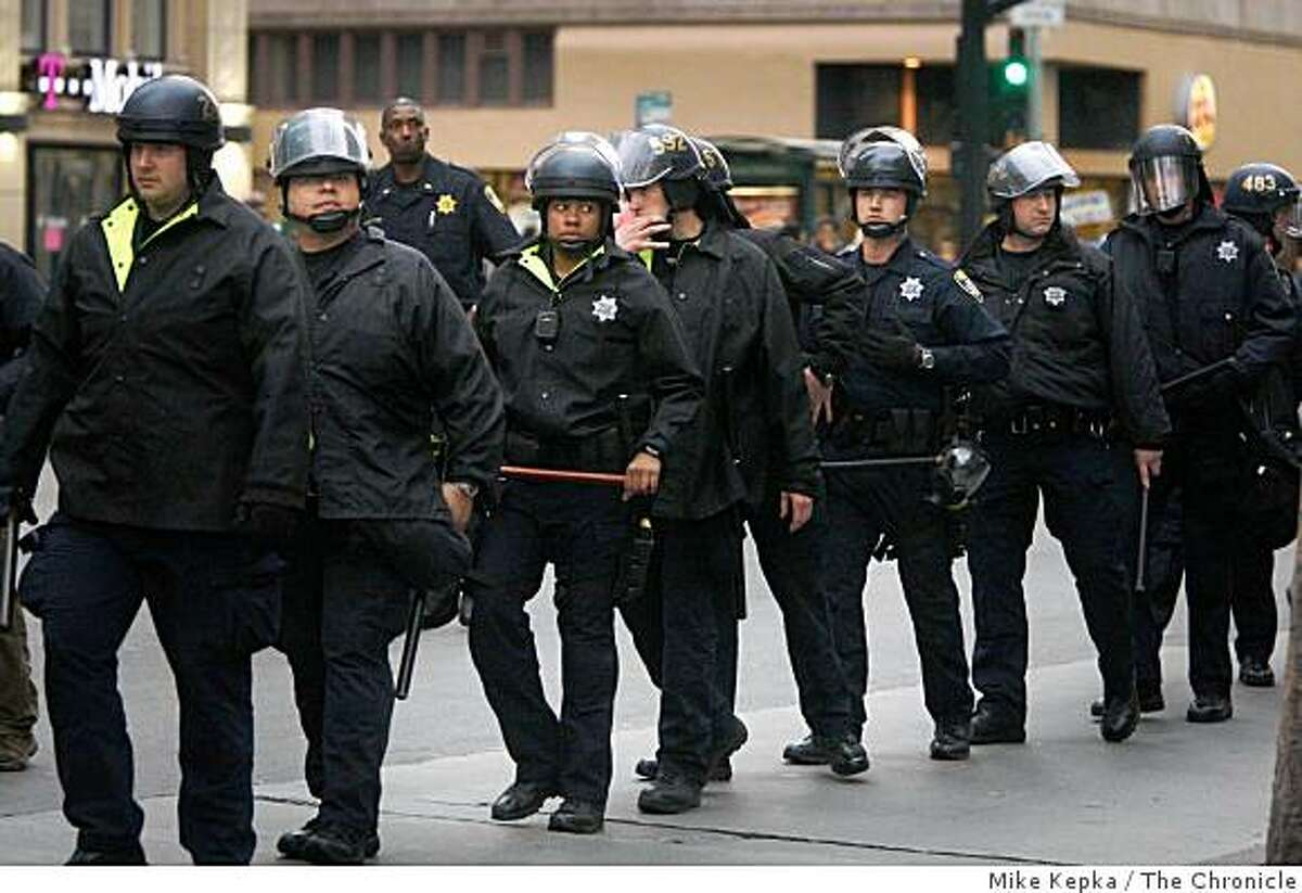 On the day BART police officer was released on bail after shooting Oscar Grant, Oakland Police dressed in riot gear watch as protesters rally near Oakland city hall on Friday Feb. 6, 2009 in Oakland, Calif.