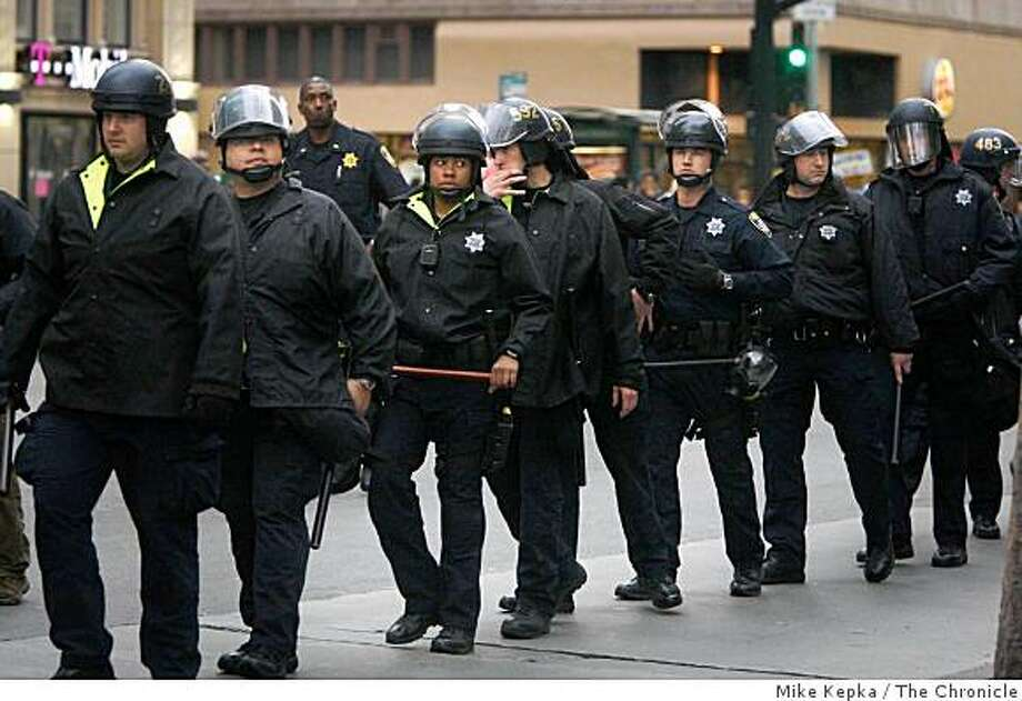 On the day BART police officer was released on bail after shooting Oscar Grant, Oakland Police dressed in riot gear watch as protesters rally near Oakland city hall on Friday Feb. 6, 2009 in Oakland, Calif. Photo: Mike Kepka, The Chronicle