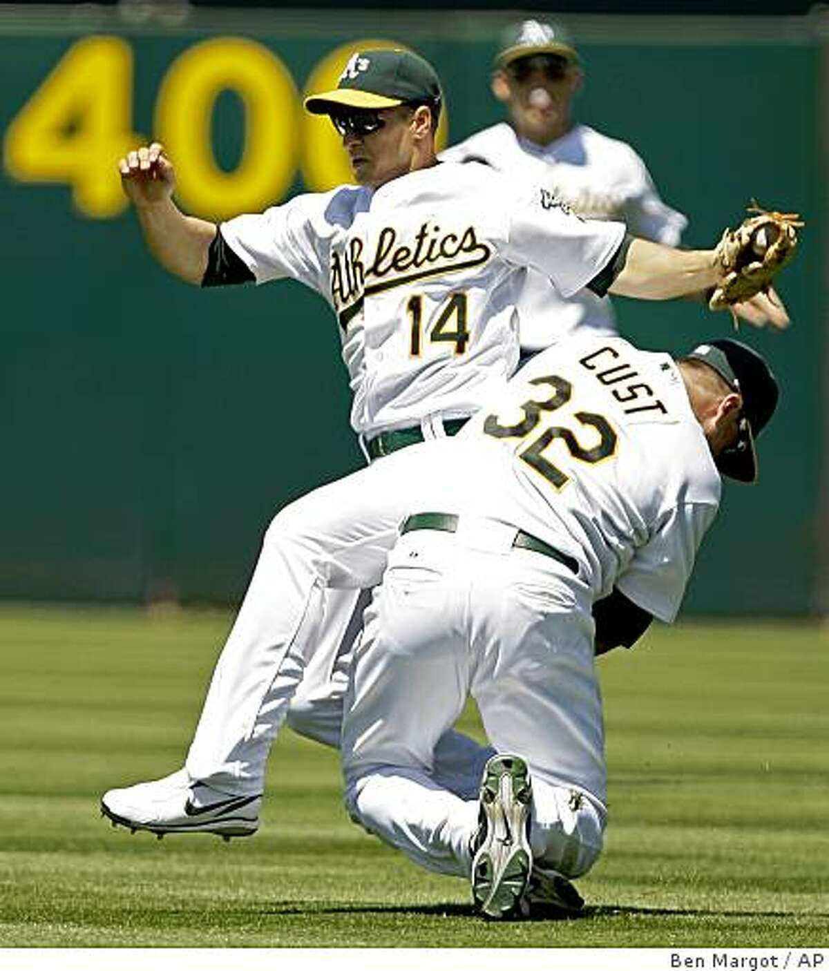 Oakland Athletics' Mark Ellis (14) collides with teammate Jack Cust after making the catch on a ball hit by Colorado Rockies' Ian Stewart in the sixth inning of a baseball game Sunday, June 28, 2009, in Oakland, Calif. (AP Photo/Ben Margot)