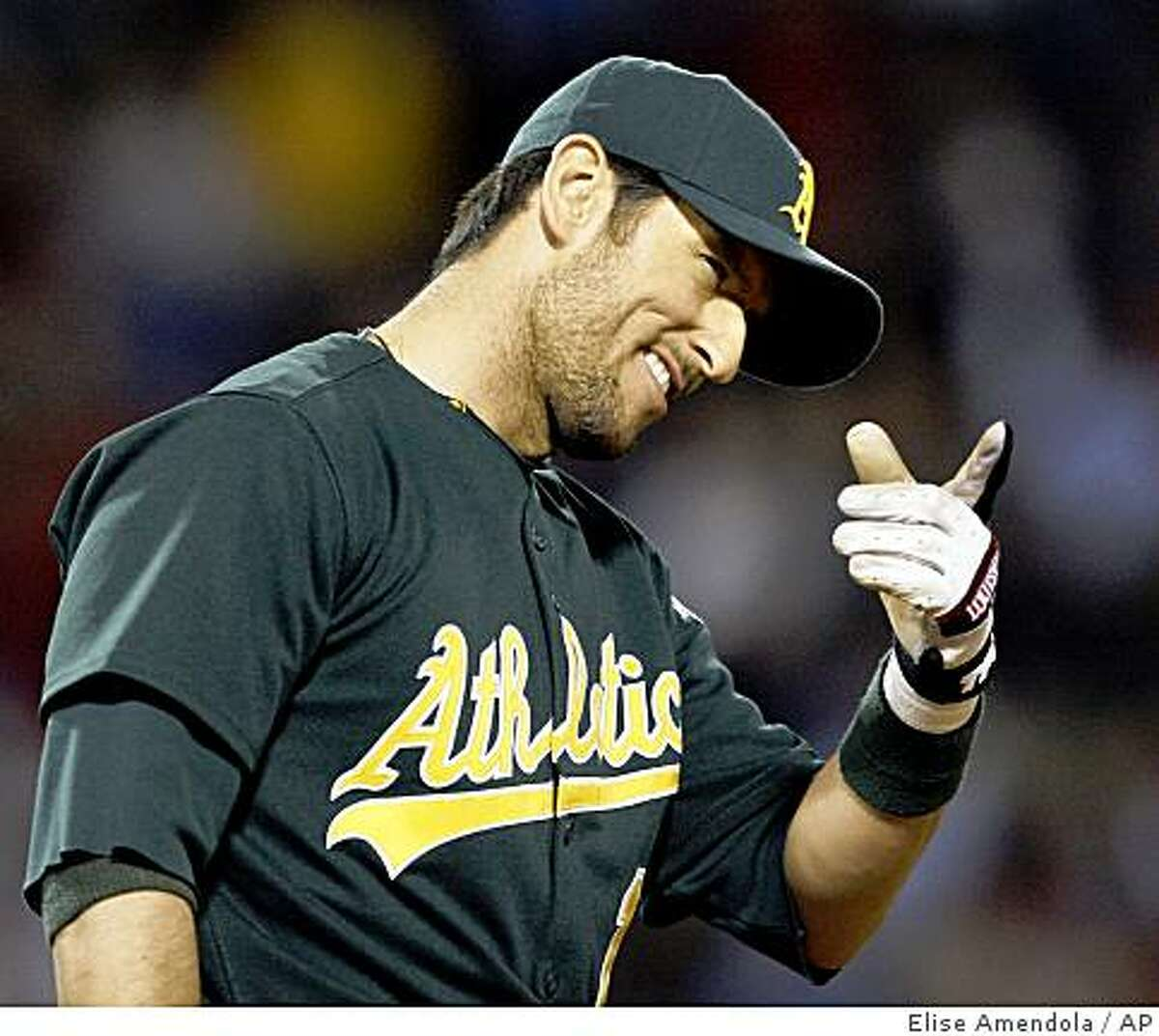 Oakland Athletics' Nomar Garciaparra, a former Boston Red Sox star player, points and smiles to fans as he takes the field during the eighth inning against the Boston Red Sox in a baseball game at Fenway Park in Boston, Wednesday, July 8, 2009. (AP Photo/Elise Amendola)