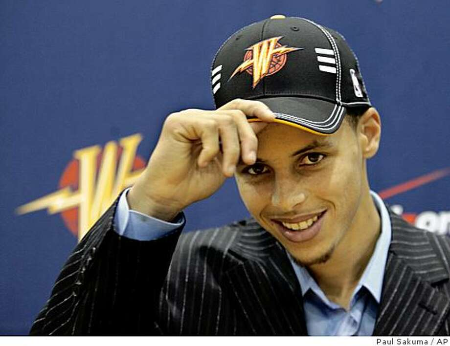 Golden State Warriors top draft pick Stephen Curry tips his hat during a news conference at the Warriors headquarters in Oakland, Calif., Friday, June 26, 2009. Curry, a guard from Davidson College, was selected No. 7 overall in the basketball draft. (AP Photo/Paul Sakuma) Photo: Paul Sakuma, AP