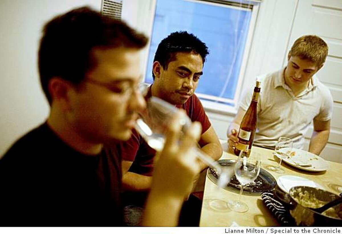 Aaron Arboleda, 27, center, and his roommates have dinner with Portuguese green wine, made from green grapes, with dinner, in San Francisco, Calif., on Tuesday, June 23, 2009.