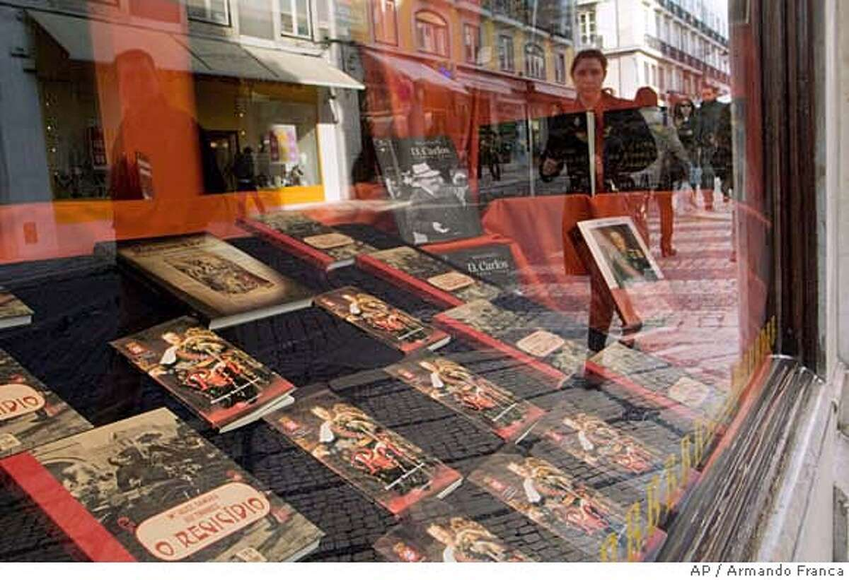 **APN ADVANCE FOR SUNDAY FEB. 17** People walk by a bookstore window decorated with books about Portugal's last King, Carlos I, and his assassination, Friday, Jan. 25 2008, in downtown Lisbon. February 1st marks the 100th anniversary of the assassination of the 44-year-old king and his eldest son Prince Luis Filipe. (AP Photo/Armando Franca) **APN ADVANCE FOR SUNDAY FEB. 17**