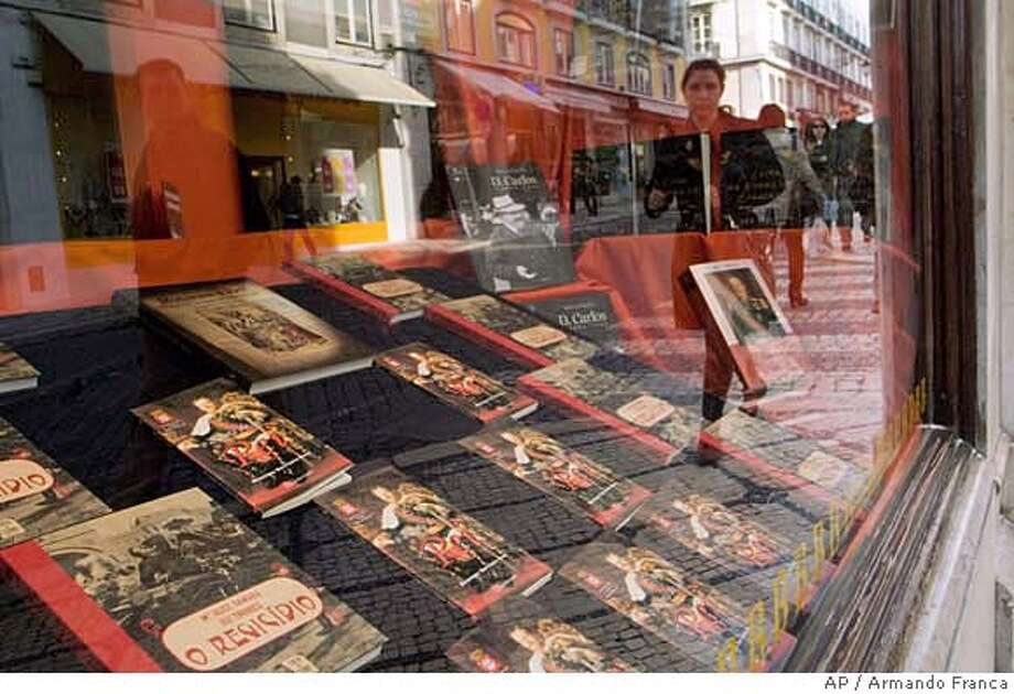 **APN ADVANCE FOR SUNDAY FEB. 17** People walk by a bookstore window decorated with books about Portugal's last King, Carlos I, and his assassination, Friday, Jan. 25 2008, in downtown Lisbon. February 1st marks the 100th anniversary of the assassination of the 44-year-old king and his eldest son Prince Luis Filipe. (AP Photo/Armando Franca) **APN ADVANCE FOR SUNDAY FEB. 17** Photo: ARMANDO FRANCA