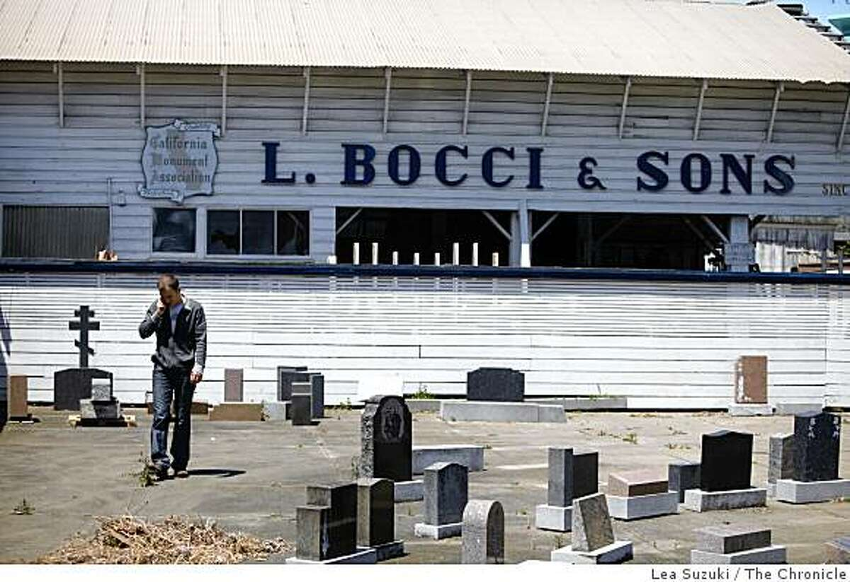 Tony Montana, who occasionally helps out at L. Bocci and Sons, talks on his cell phone while walking among tombstones left on display by the previous owners on Wednesday June 24, 2009 in Colma, Calif.