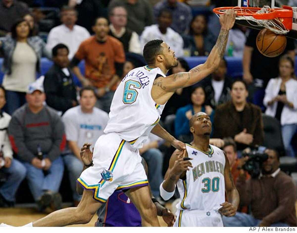 New Orleans Hornets center Tyson Chandler, top, dunks the ball as forward David West, right, watches during the first half of an NBA basketball game against the Phoenix Suns in New Orleans on Wednesday, Feb. 27, 2008. (AP Photo/Alex Brandon) EFE OUT