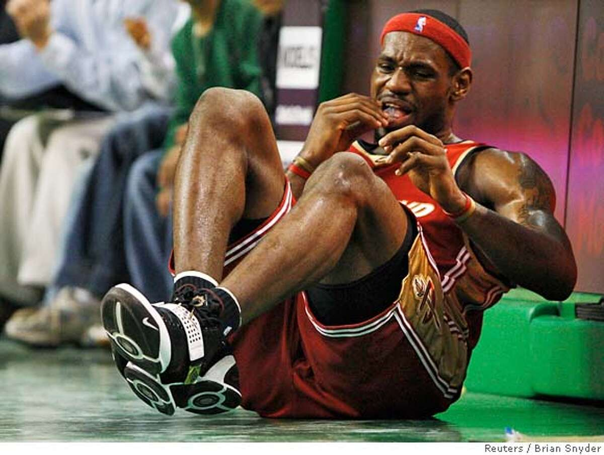 Cleveland Cavaliers forward LeBron James sits on the side of the court after suffering an injury in the second quarter of their NBA basketball game against Boston Celtics in Boston, Massachusetts February 27, 2008. REUTERS/Brian Snyder (UNITED STATES) 0