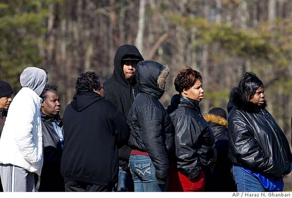 Family and friends gather along a roadway as they wait for information from emergency personnel investigating a car crash on Indian Head Highway, Saturday, Feb. 16, 2008, in Accokeek, Md. A car plowed into a crowd that had gathered to watch a drag race on the suburban road early Saturday, killing seven people and injuring at least four, police said. (AP Photo/Haraz N. Ghanbari)
