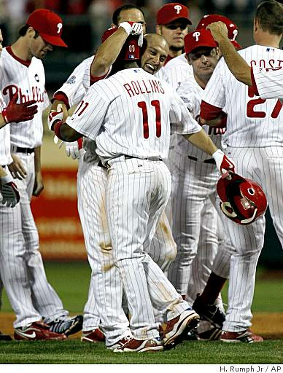 Philadelphia Phillies' Shane Victorino, center, celebrates with Jimmy Rollins (11) after Victorino hit a one run single against the Cincinnati Reds' to win the game 3-2 in the ninth inning of a baseball game, Wednesday, July 8, 2009, in Philadelphia. (AP Photo/H. Rumph Jr.)