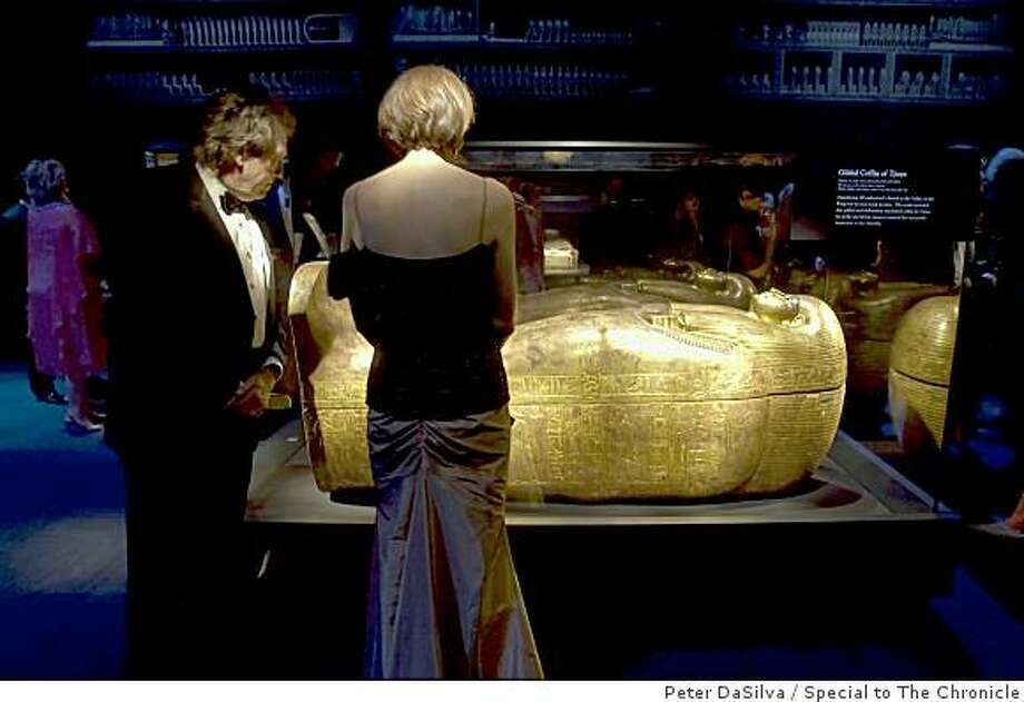"Guests Doug and Jennifer Biederbeck of the Tutankhamun and the Golden Age of the Pharaohs opening gala, looks at a ""Gilded Coffin of Tjuya"" in the Tutankhamun exhibit at the de Young Museum in San Francisco, California on Jun. 23, 2009. Photo: Peter DaSilva, Special To The Chronicle"