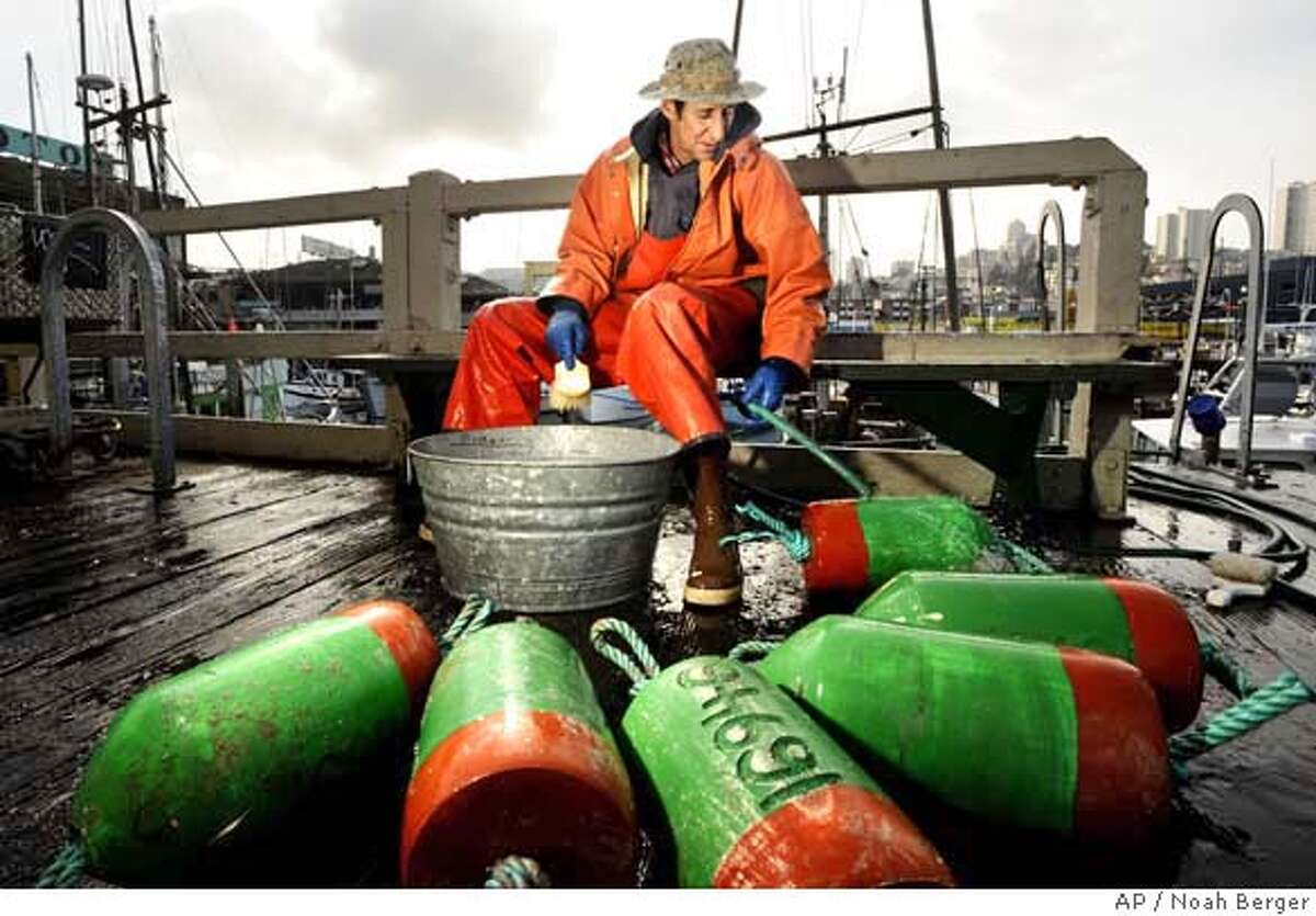 **FOR USE ON SUNDAY, FEB. 3, AND THEREAFTER**rFisherman Tim Calvert cleans buoys at Fishermans Wharf on Friday, Feb. 1, 2008, in San Francisco. Federal fishery regulators said this past week that the number of chinook salmon returning to the Sacramento River and its tributaries last fall was astonishingly low. That could trigger severe fishing restrictions and economic hardship for fishermen and related businesses from Central California to the Canadian border. (AP Photo/Noah Berger) FOR USE ON SUNDAY, FEB. 3, AND THEREAFTER