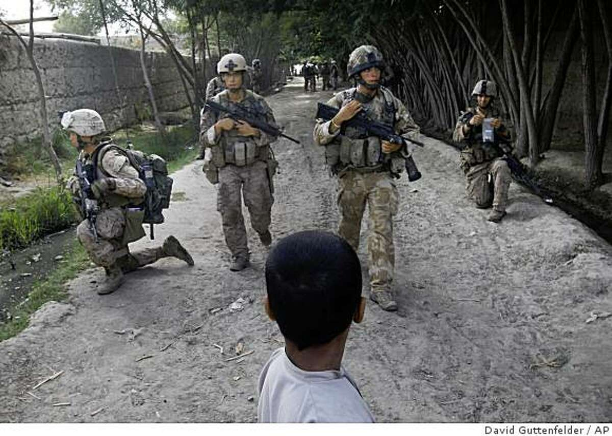 ** CORRECTS DAY OF WEEK ** An Afghan boy looks on as British troops training the Afghan National Army and U.S. Marines from the 2nd MEB, 1st Battalion 5th Marines patrol through a village in the Nawa district in Afghanistan's Helmand province, Sunday, July 5, 2009. (AP Photo/David Guttenfelder)