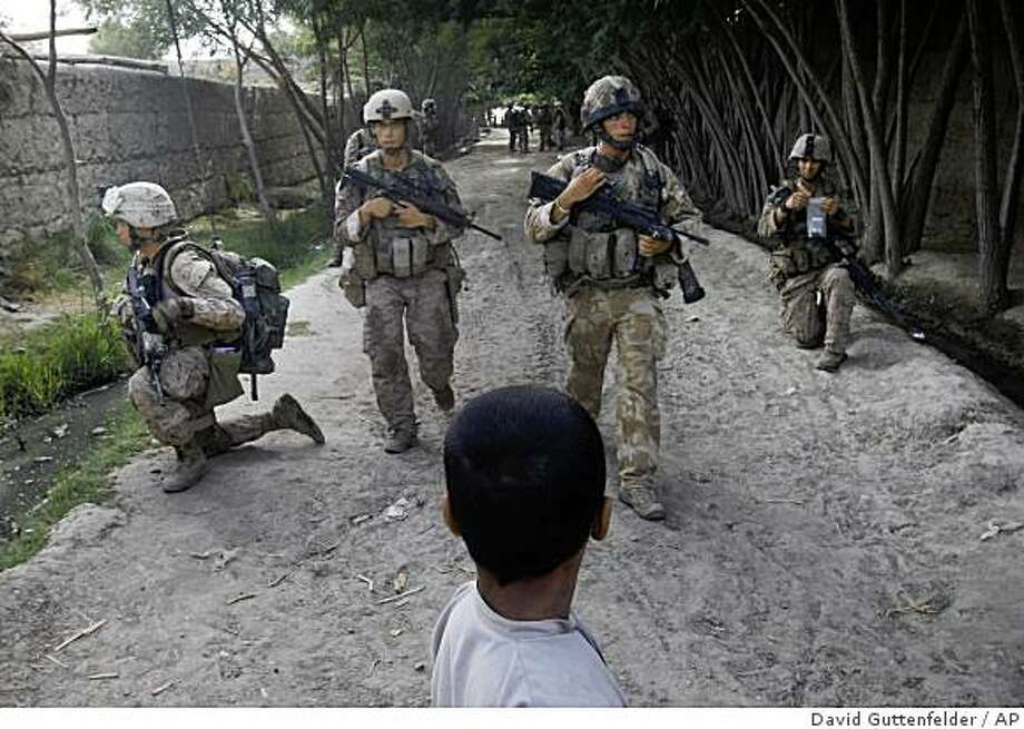 ** CORRECTS DAY OF WEEK ** An Afghan boy looks on as British troops training the Afghan National Army and U.S. Marines from the 2nd MEB, 1st Battalion 5th Marines patrol through a village in the Nawa district in Afghanistan's Helmand province, Sunday, July 5, 2009. (AP Photo/David Guttenfelder) Photo: David Guttenfelder, AP