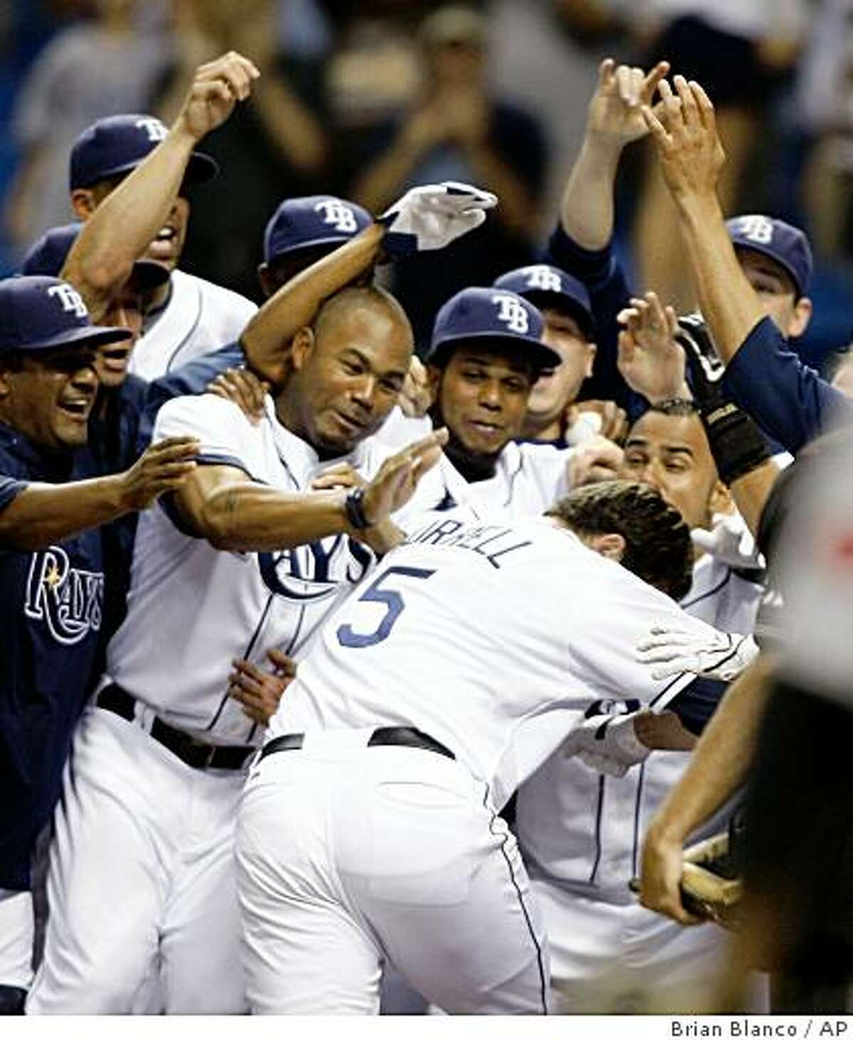 Tampa Bay Rays' Pat Burrell is surrounded by his teammates after hitting a two-run home run against the Toronto Blue Jays in the 11th inning of a baseball game Tuesday, July 7, 2009, in St. Petersburg, Fla. Tampa Bay won 3-1. (AP Photo/Brian Blanco)