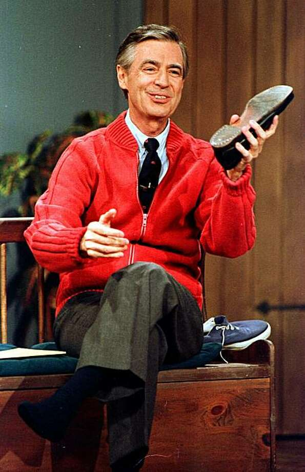 "** FILE ** Fred Rogers rehearses the opening of his PBS show ""Mister Rogers' Neighborhood"" during a taping in this June 28, 1989, file photo in Pittsburgh. A tribute to children's public television pioneer Fred Rogers will include an effort to get people everywhere to wear a sweater on what would have been his 80th birthday.  Family Communications Inc. of Pittsburgh is promoting March 20, 2008, as ""Sweater Day"" to honor Rogers, who died of cancer five years ago. A sweater was his trademark garb on ""Mister Rogers' Neighborhood.""  (AP Photo/Gene J. Puskar) Photo: Gene J. Puskar, AP"