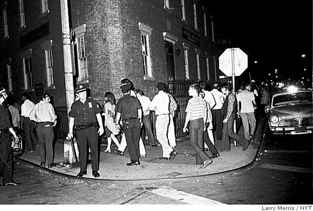 Three police officers kept a tight rein on a crowd to keep them on the sidewalks and off the streets at the corner of Waverly Place and Christopher Steet, half a block from the Stonewall Inn. The image was shot by Times photographer Larry Morris on the evening of Wednesday, July 2, 1969, five nights after a raid on the Stonewall Inn, a nightclub on Christopher Street popular among gay men and lesbians, touched off the disturbances. The Stonewall uprising that began 40 years ago this month has come to be seen as a defining event in the development of the gay rights movement. (Larry Morris/The New York Times)