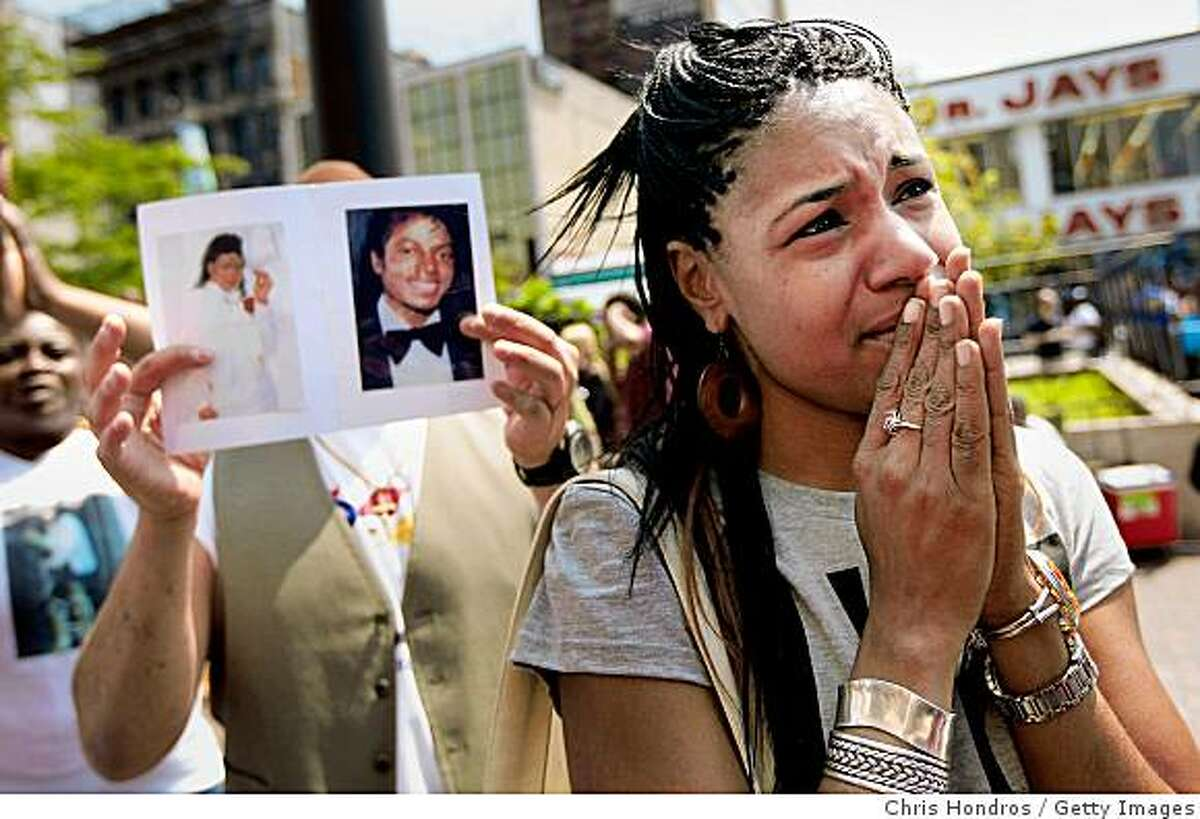 NEW YORK - JULY 07: Yvette Russell (R) of Harlem cries during a broadcast of the memorial for pop singer Michael Jackson in the Harlem neighborhood July 7, 2009 of New York City. Fans around the world watched and celebrated the pop singer's memory today, as a throng of celebrities and fans descend onto Jackson's memorial service in Los Angeles. (Photo by Chris Hondros/Getty Images)