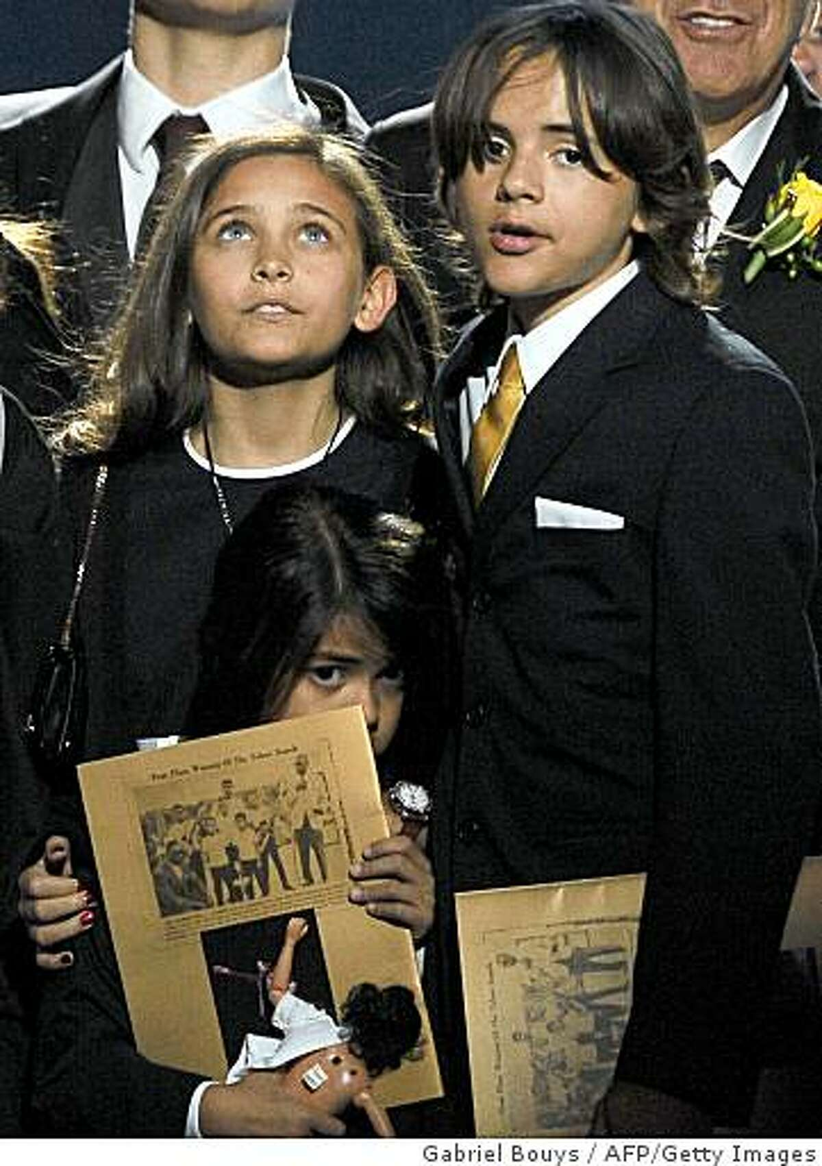 Michael Jackson's children from left Paris Michael Katherine Jackson (L), Prince Michael Jackson II (also known as Blanket) and Prince Michael Jackson I stand during a memorial service for their father, music legend Michael Jackson, at the Staples Center in Los Angeles on July 7, 2009. AFP PHOTO/GABRIEL BOUYS/POOL (Photo credit should read GABRIEL BOUYS/AFP/Getty Images)