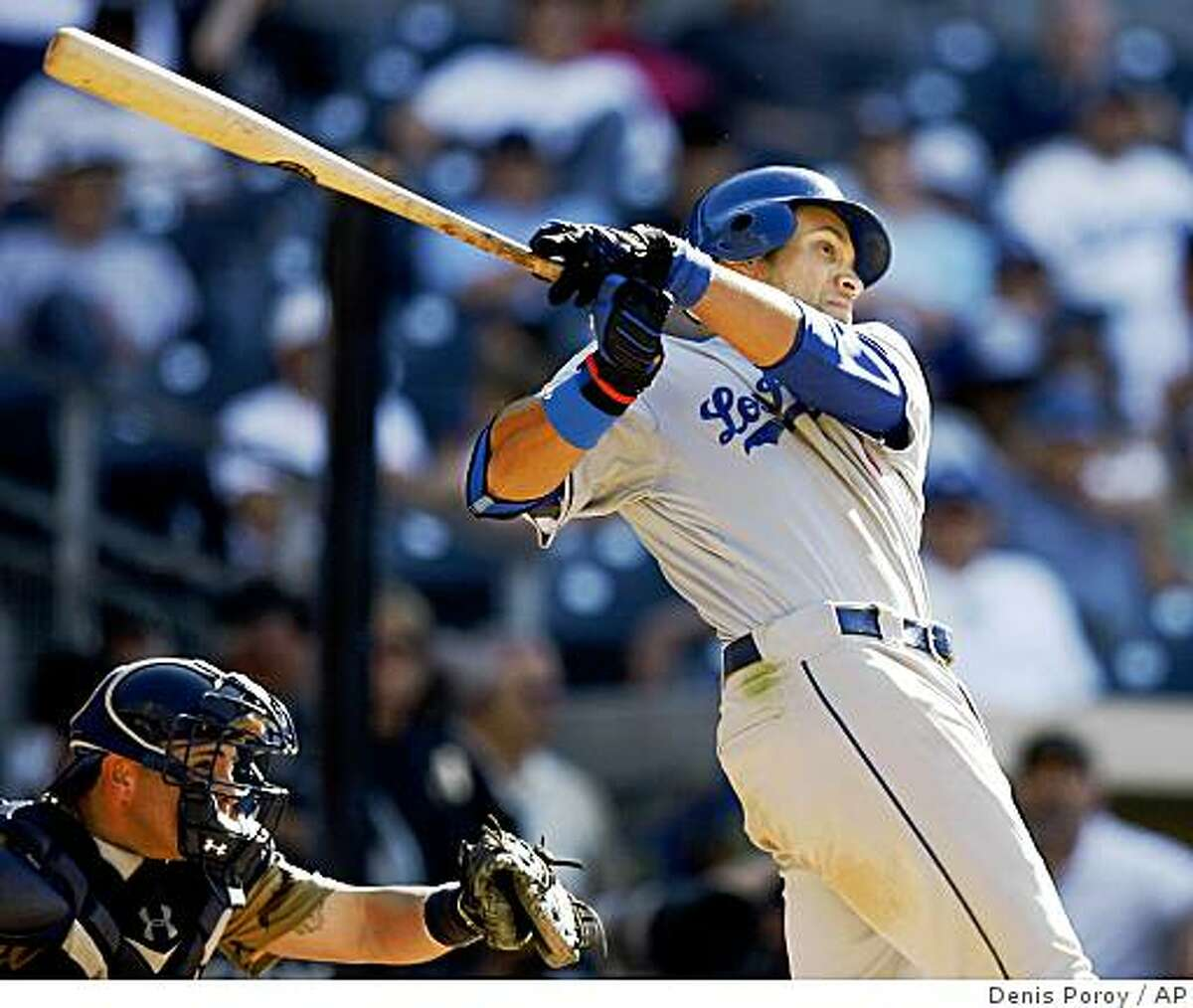 Los Angeles Dodgers' James Loney, right, connects for a go-ahead solo home run as San Diego Padres catcher Eliezer Alfonzo, left, looks on during the 13th inning of a baseball game Sunday, July 5, 2009, in San Diego. The Dodgers won 7-6. (AP Photo/Denis Poroy)