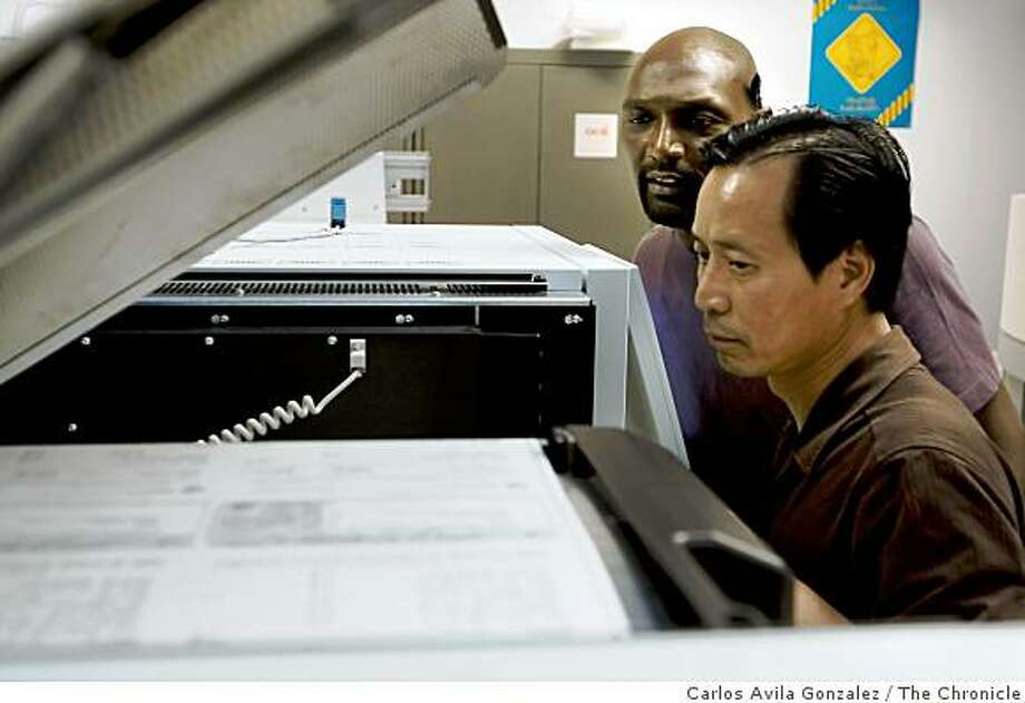 James McCullough, rear, and Michael Yu, check the feed on a machine printing the State of California registered warrants at the State Controller's office in Sacramento, Calif., on Thursday, July 2, 2009. The first batches of IOUs went out today and we have a chance to photograph the printing of the checks. Aside from the daily, this would be a good opportunity to shoot the checks for files. Photo: Carlos Avila Gonzalez, The Chronicle
