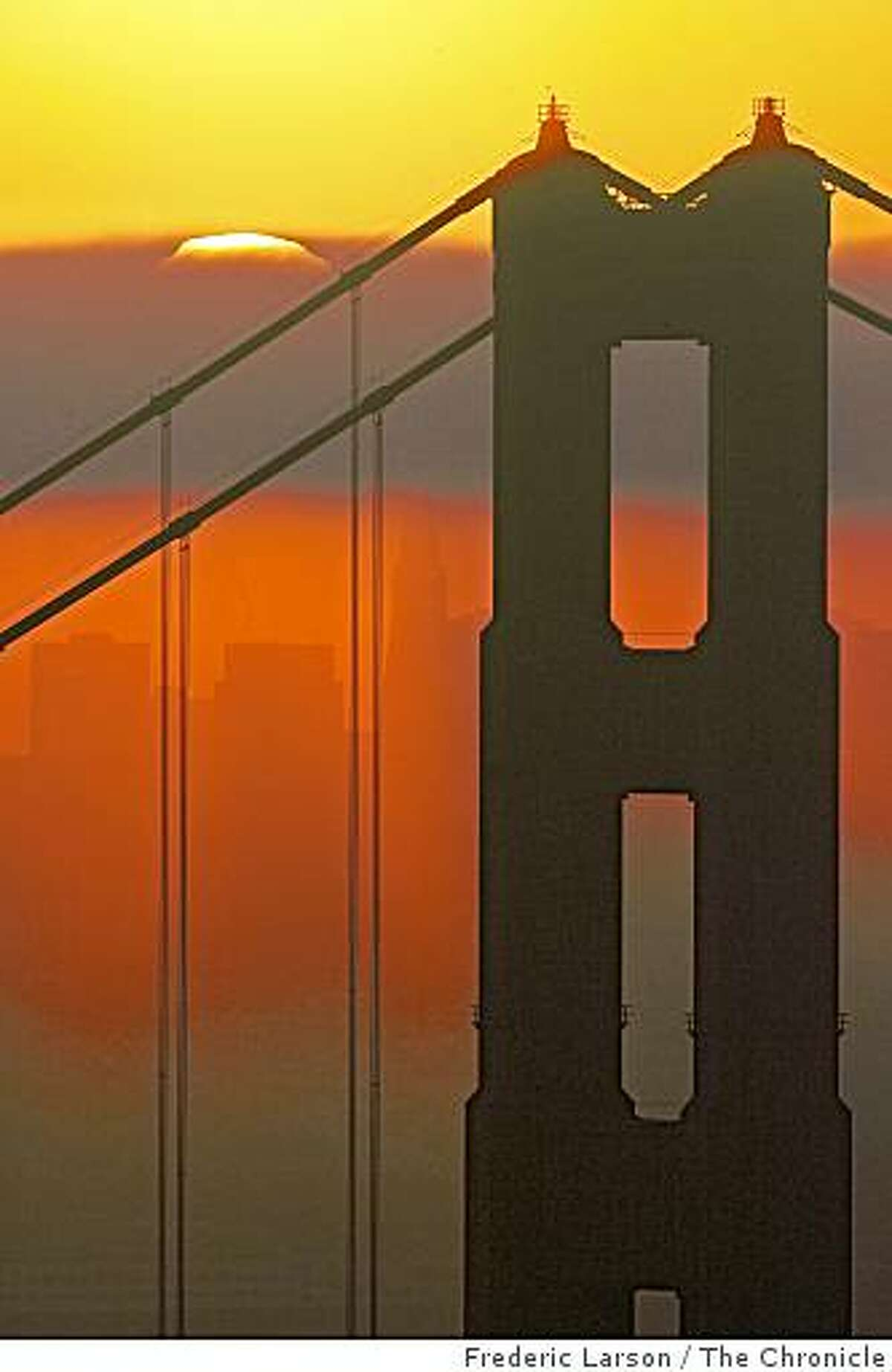 The sun rose through a thin bank of fog resting near the top of the north tower of the Golden Gate Bridge.