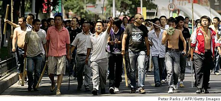 A large group of Han Chinese walk up a street carry sticks and shovels on the streets in Urumqi in China's far west Xinjiang province on July 7, 2009. Police on July 7 fired clouds of acrid tear gas to disperse thousands of Han Chinese protesters armed with makeshift weapons, as chaos gripped this flashpoint city riven by ethnic tensions. Thousands of heavily armed police deployed across Urumqi, the capital of China's remote northwest Xinjiang region, but tensions spiked dramatically following weekend rioting that claimed at least 156 lives.       TOPSHOTS/AFP PHOTO/Peter PARKS (Photo credit should read PETER PARKS/AFP/Getty Images) Photo: Peter Parks, AFP/Getty Images