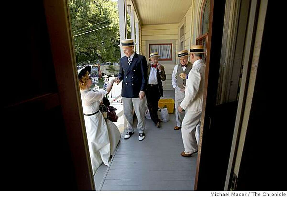 Ann Gibson, (left) is greeted by Federick Hodges, during the 4th of July celebration at the Historic Pardee Home on Saturday July 4, 2009, in downtown Oakland, Calif. Others in period dress for the 1908 Patriotic PInic are, David Banks, (center), Sean Sharp, and Joe DiPietro, (right).