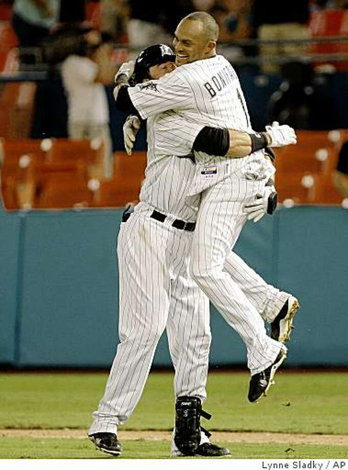 Florida Marlins' Jorge Cantu, left, hugs Emilio Bonifacio, right, after Bonifacio scored on a single by Cantu in the 12th inning to win 7-6 over the Baltimore Orioles during an interleague baseball game at Land Shark Stadium in Miami Tuesday, June 23, 2009.  (AP Photo/Lynne Sladky) Photo: Lynne Sladky, AP