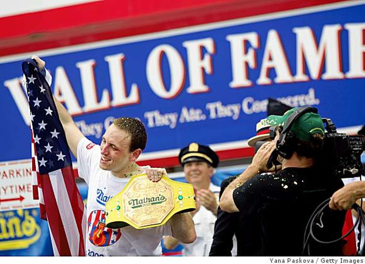 NEW YORK - JULY 4: Joey Chestnut (L) of San Jose, California holds up the American flag and his champion belt after defeating Takeru Kobayashi of Nagano, Japan and Patrick