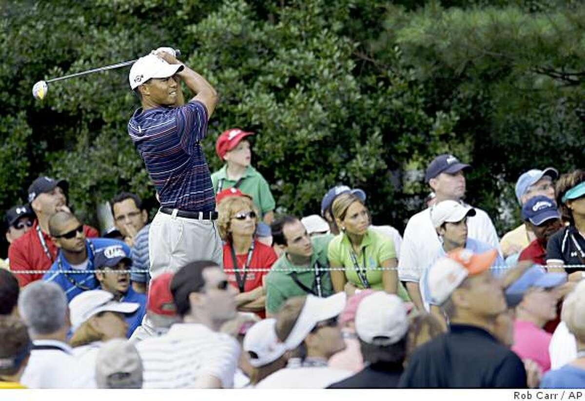 Tiger Woods follows his tee shot on the 17th hole during the second round of the AT&T National golf tournament at Congressional Country Club, Friday, July 3, 2009, in Bethesda, Md. (AP Photo/Rob Carr)