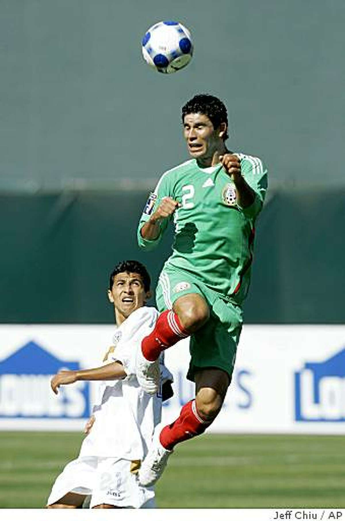 Mexico's Jonny Magallon, top, heads the ball in front of Nicaragua's David Martinez in the first half of a CONCACAF Gold Cup soccer match Sunday, July 5, 2009, in Oakland, Calif. (AP Photo/Jeff Chiu)