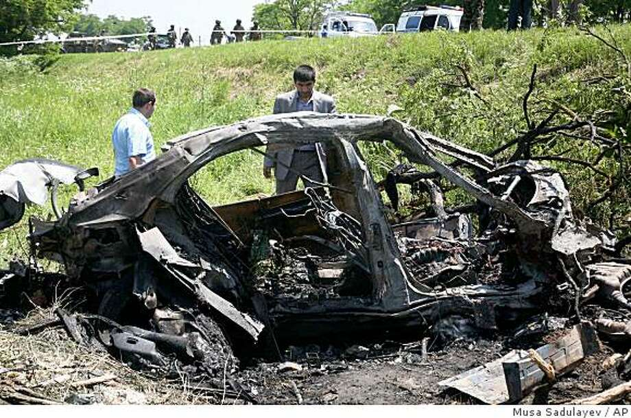 Police and military investigators examine the scene of an explosion in the North Caucasus republic of Ingushetia, near Nazran, Monday June 22 2009. A suicide car bomber attacked the convoy that the president of the troubled Russian region of Ingushetia, Yunus-Bek Yevkurov , was traveling in Monday, critically wounding the president and killing or wounding others. (AP Photo/Musa Sadulayev) Photo: Musa Sadulayev, AP