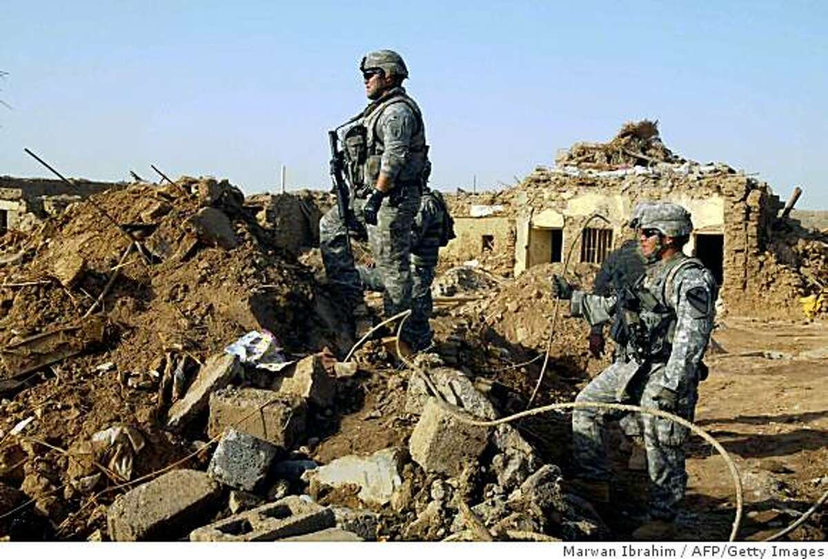 US Army soldiers survey the damage from a truck bomb that exploded the day before in the northern Iraqi city of Kirkuk on June 21, 2009. The truck bomb killed 64 people near the northern Iraqi oil city of Kirkuk on June 20, the country's bloodiest attack in 15 months just 10 days before US troops are due to quit urban areas. AFP PHOTO/MARWAN IBRAHIM (Photo credit should read MARWAN IBRAHIM/AFP/Getty Images)