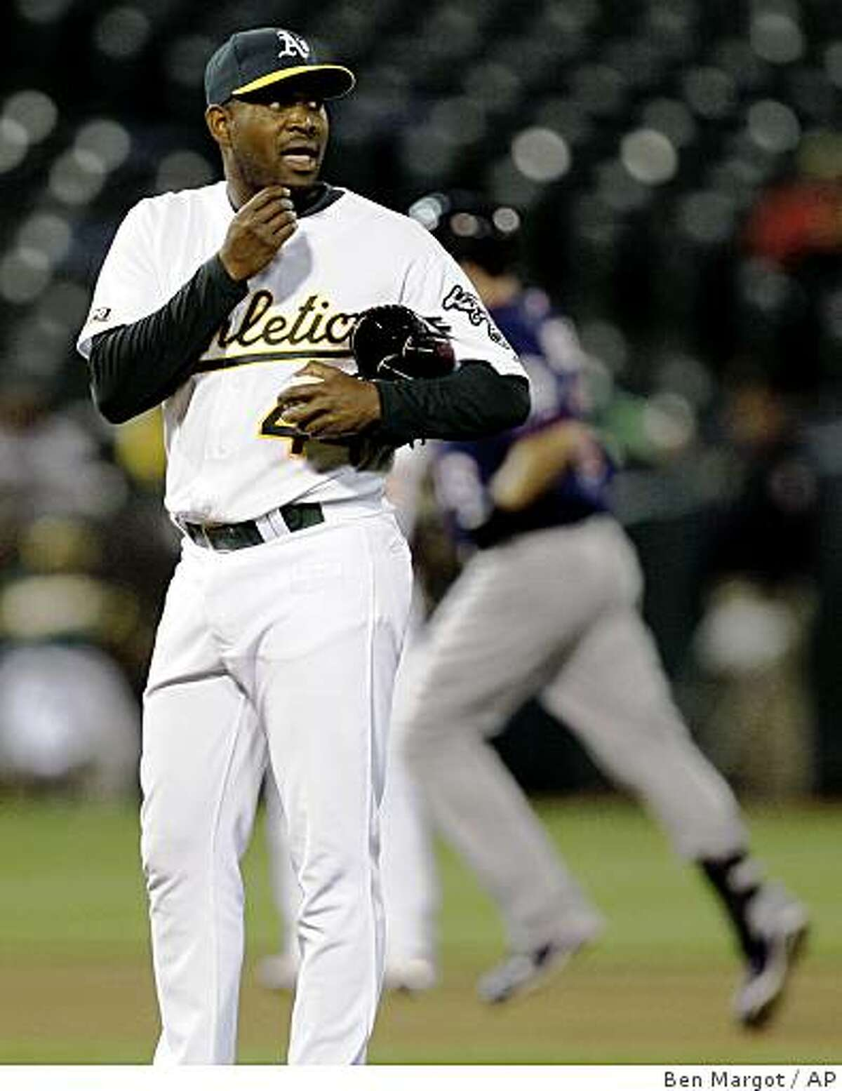 Oakland Athletics' Santiago Casilla, left, waits for Minnesota Twins' Jason Kubel to run the bases after giving up a three-run home run to Kubel in the seventh inning of a baseball game Tuesday, June 9, 2009, in Oakland, Calif. (AP Photo/Ben Margot)
