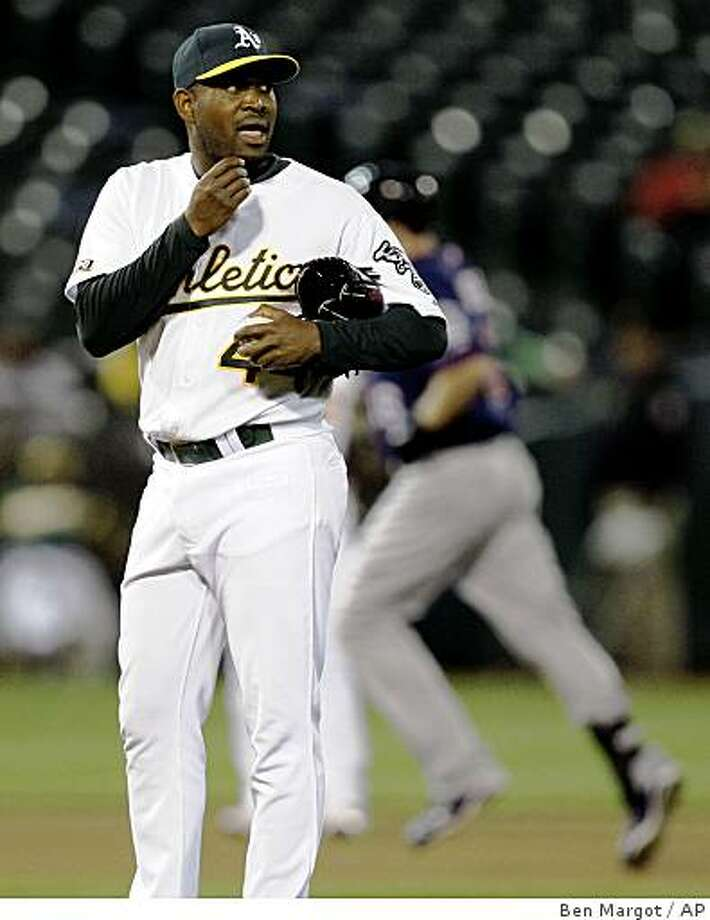 Oakland Athletics' Santiago Casilla, left, waits for Minnesota Twins' Jason Kubel to run the bases after giving up a three-run home run to Kubel in the seventh inning of a baseball game Tuesday, June 9, 2009, in Oakland, Calif. (AP Photo/Ben Margot) Photo: Ben Margot, AP
