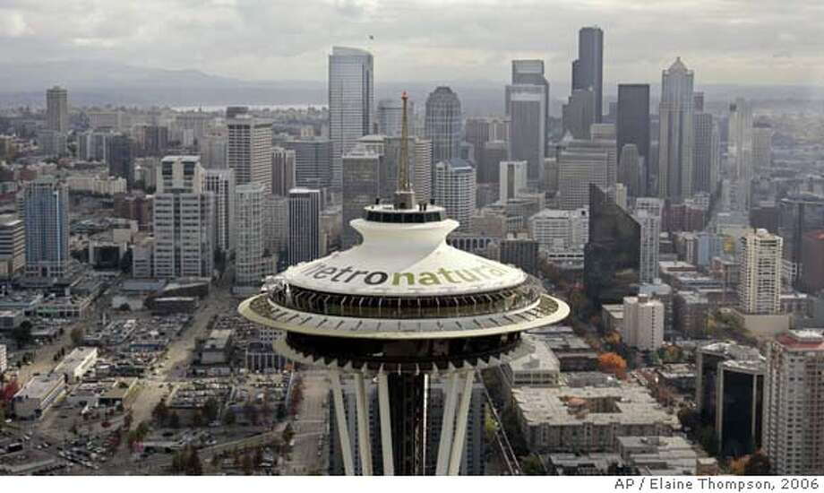 """Letters 18-feet tall proclaiming Seattle's newest tourism slogan, """"metronatural,"""" are seen atop the landmark Space Needle Friday, Oct. 20, 2006, just north of downtown Seattle. The new tagline was unveiled earlier in the day by the Seattle Convention and Visitors Bureau to promote the city. (AP Photo/Elaine Thompson)  Ran on: 10-22-2006  &quo;Metronatural,&quo; a play on &quo;metrosexual&quo; meant to evoke Seattle's urban and wilderness draws, is unveiled on the Space Needle. Photo: ELAINE THOMPSON"""